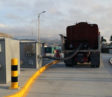 A hauler uses a Portalogic waste dump station, which collects data about the load and syncs with Portalogic Management Software.